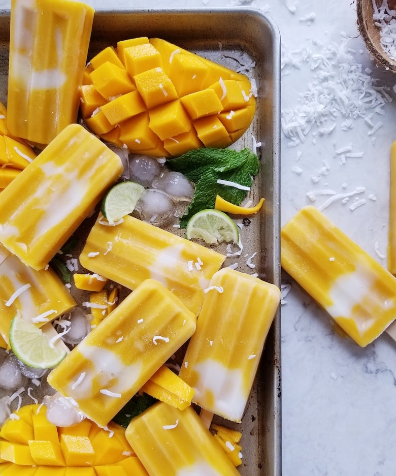 Tray of mango popsicles with ice and half a mango