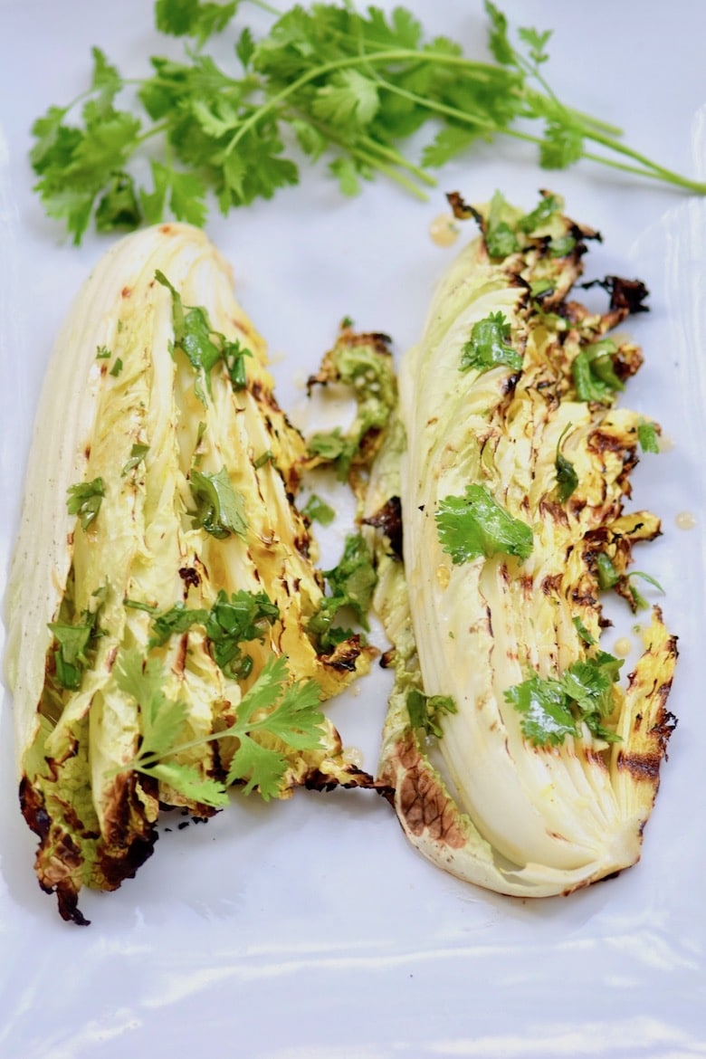 BBQ Chinese Cabbage on a white tray with a several sprigs of herbs
