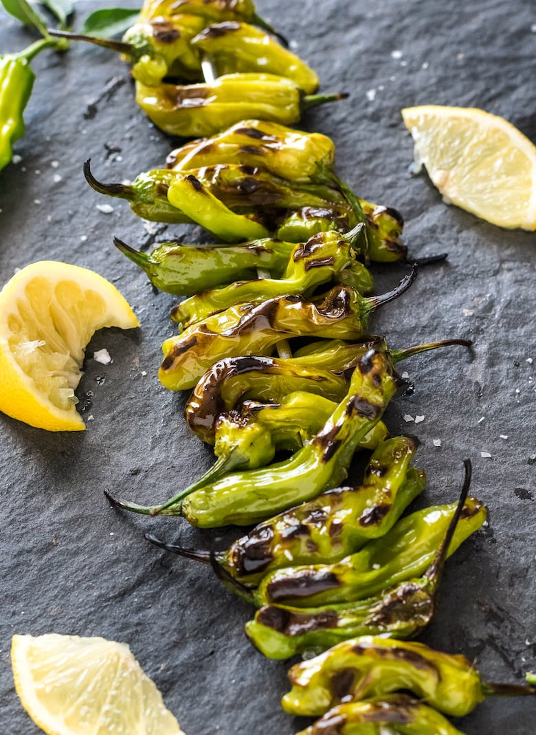 BBQ grilled shishito peppers lined up on a charcoal surface with lemon wedges