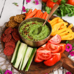 colourful platter of vegetables and crackers centred around a green avocado dip - perspective shot