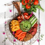 colourful platter of vegetables and crackers centred around a green avocado dip - flatlay