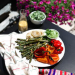 plate of grilled asparagus, colourful bell peppers and onion on a tables outside surrounded by pink flowers