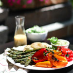 plate of grilled asparagus, colourful bell peppers and onion on a tables outside with a side green salad and a bottle of dressing