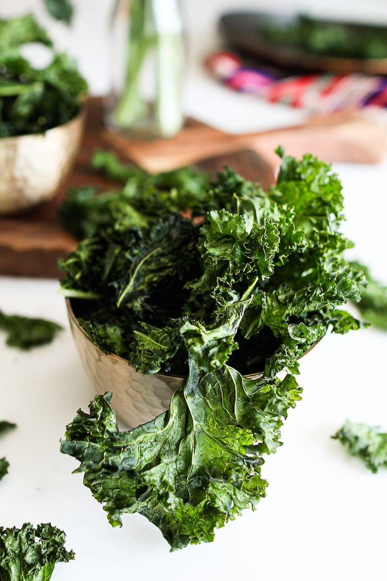 bowl of kale chips on a white work top with a board in the background with a ramekin of spice and a red shawl