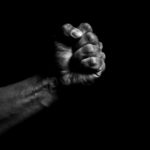 Fist of a Black person against a black background