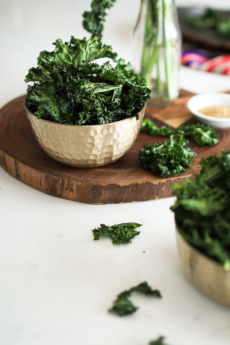 bowl of kale chips on a a wooden board