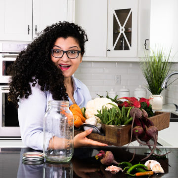 a woman holding a box of fresh vegetables standing in front of a mason jar in a kitchen with a happy shocked expression on her face.