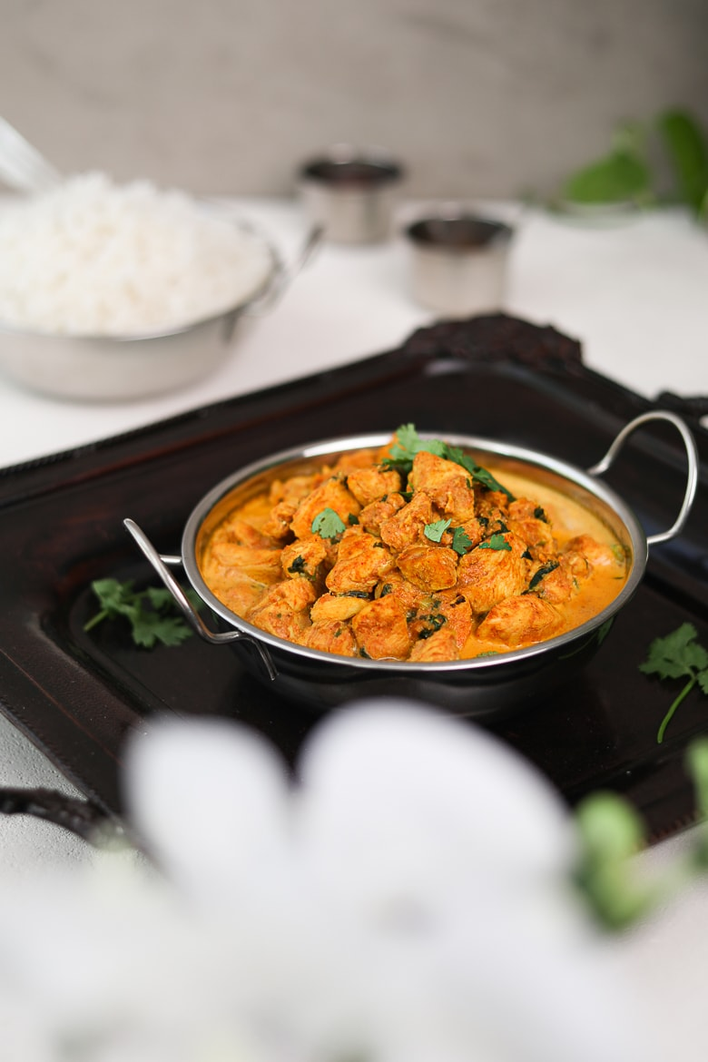 bowl of indian butter chicken on a black tray with white rice in the background and small spice containers arranged around - perspective shot