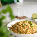 a bowl of cooked quinoa garnished with cilantro leaves and lime wedges with a a glass of sparking water in the background.