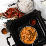 bowl of indian butter chicken on a black tray with white rice on the side flat lay