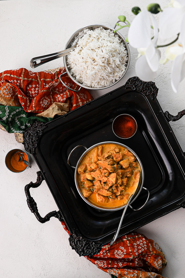 bowl of indian butter chicken on a black tray with white rice on the side and a decorative shawl - flat lay