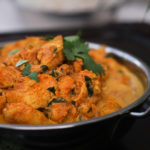 bowl of indian butter chicken garnished with cilantro - perspective shot