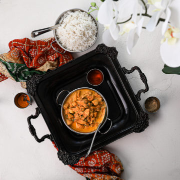 bowl of indian butter chicken on a black tray with white rice on the side placed on top of a decorative shawl flat lay