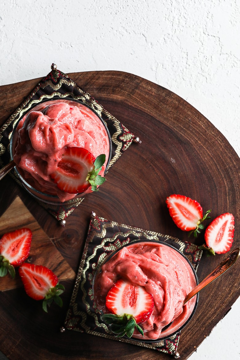 flat-lay: two glasses filled with scoops of strawberry nice cream topped with fresh strawberries and displayed on a wooden board