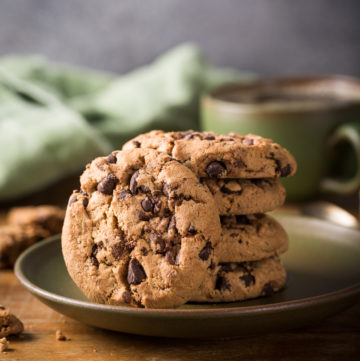 Chocolate chip cookies on green plate with cup of coffee on old wooden table. Selective focus.