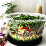 glass bowl with layers of grilled vegetables and leafy greens with a dressing bottle in the background