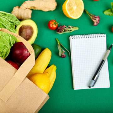 Shopping list, recipe book, diet plan. Grocering concept. Full paper bag of different fruits and vegetables, ingredients for healthy cooking on a color background. healthy food. Diet or vegan food, vegetarian. Top view. Flat lay.