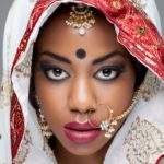 Young Indian woman in traditional clothing with bridal makeup an