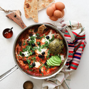 close up of a pan of shakshuka with eggs garnished with olives, herbs, avocado slices and artichoke, with a bowl of raw eggs and naan bread close by - flatlay