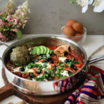 a pan of shakshuka with eggs on a wooden board garnished with olives, herbs, avocado slices and artichoke, with a bowl of raw eggs and flowers in the background - perspective