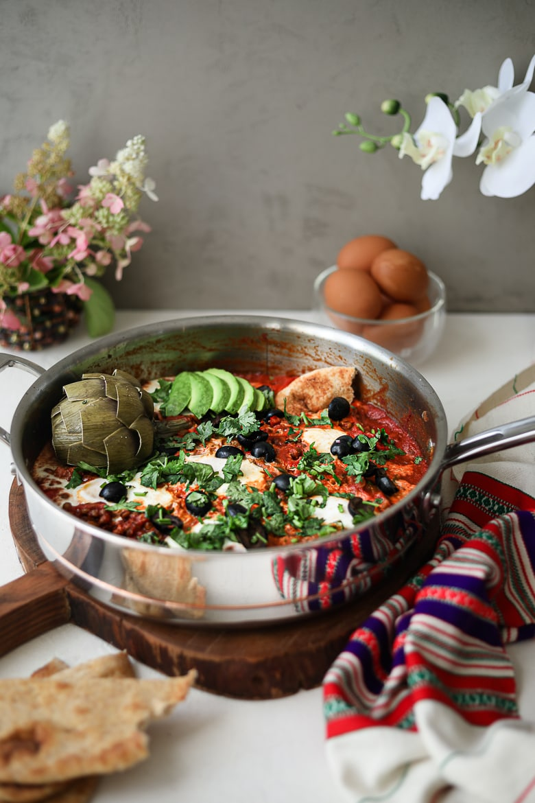 a pan of shakshuka with eggs on a wooden board garnished with olives, herbs, avocado slices and artichoke, with a bowl of raw eggs and flowers in the background - for Ramadan 2021
