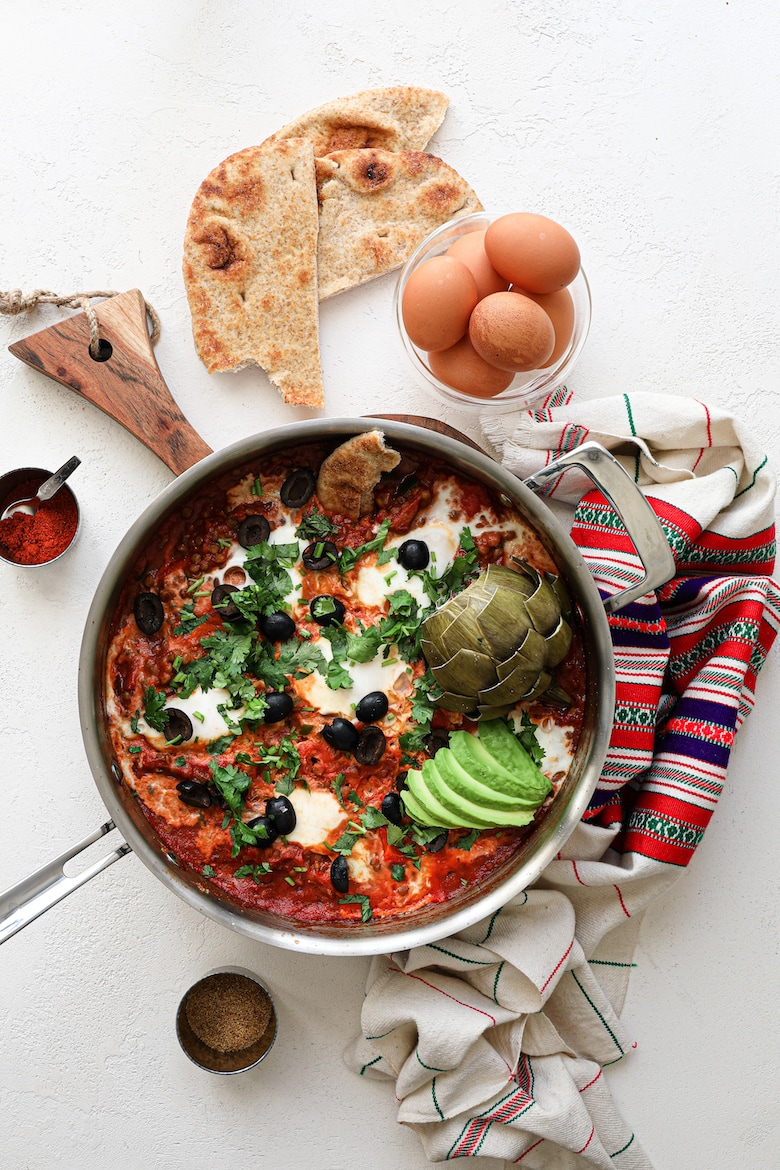 a pan of shakshuka with eggs garnished with olives, herbs, avocado slices and artichoke, with a bowl of raw eggs and naan bread close by - flatlay