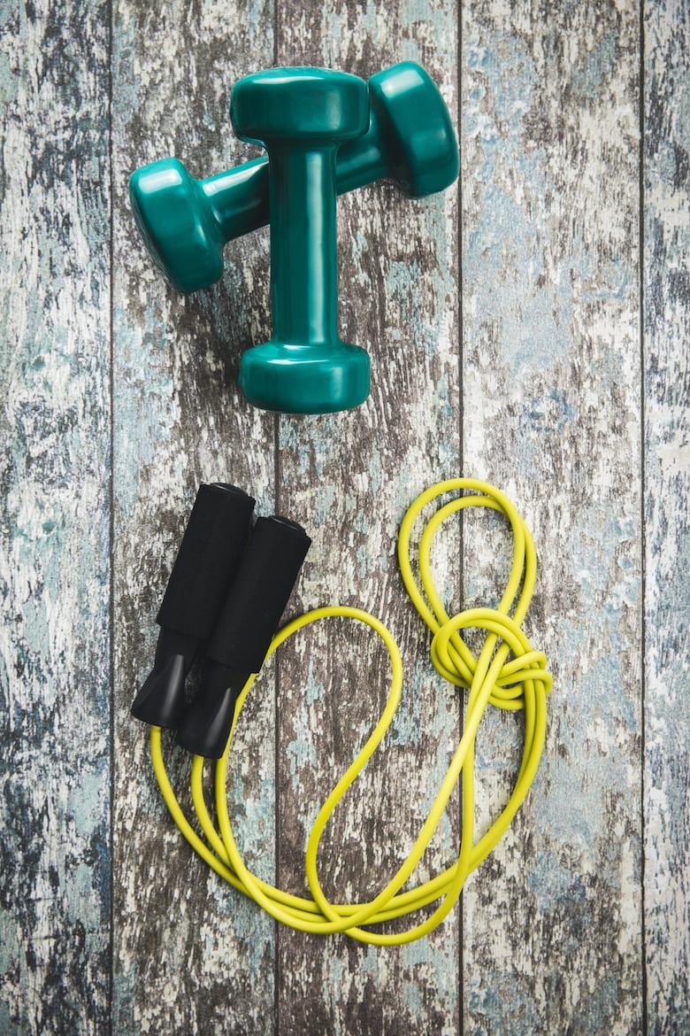 Green dumbbells and jump rope on vintage background. Top view.