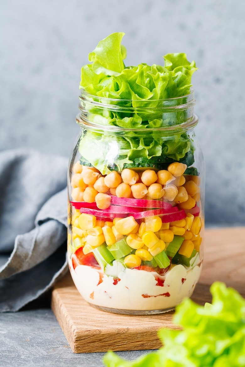 Single jar with layering vegan salad for healthy lunch with place for text. The concept of fitness and vegetarian food.