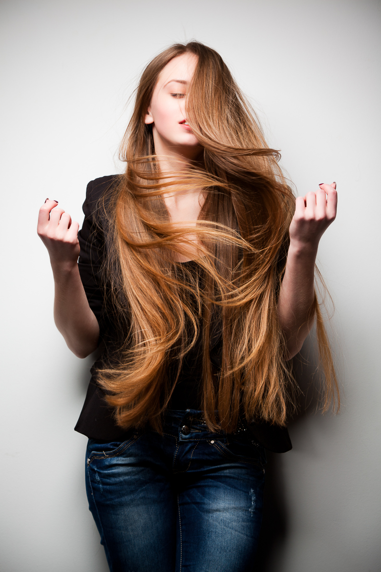 Girl dressed in black jacket, with long flowing hair, posing with her head turned to side against white wall