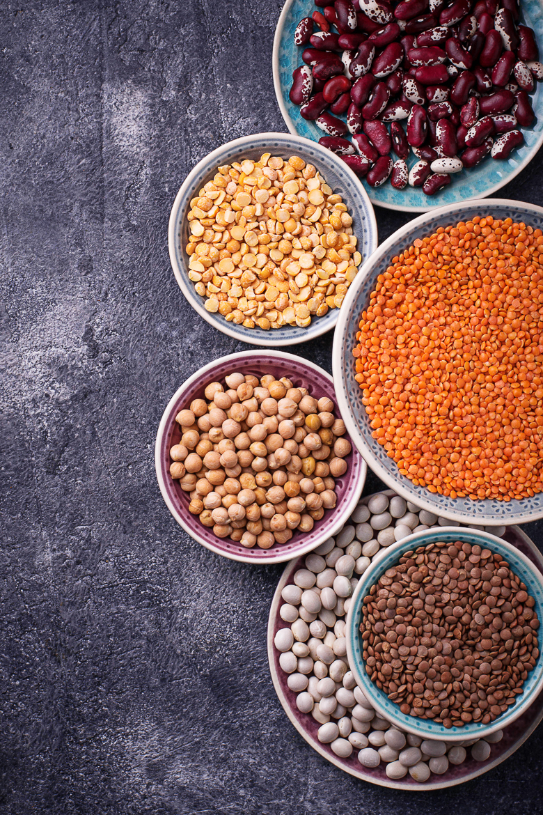 Various legumes. Chickpeas, red lentils, black lentils, yellow peas and beans. Selective focus. Top view