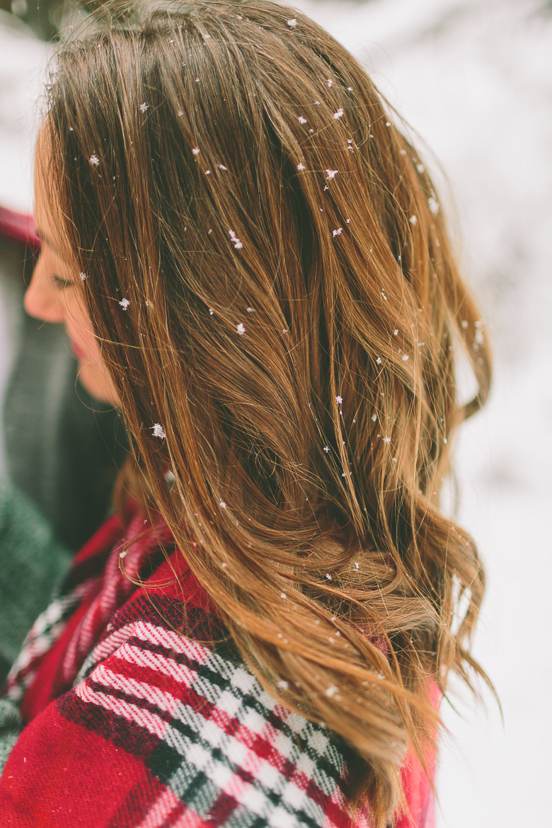 side view of a lady with long beautiful hair standing outside in the snow