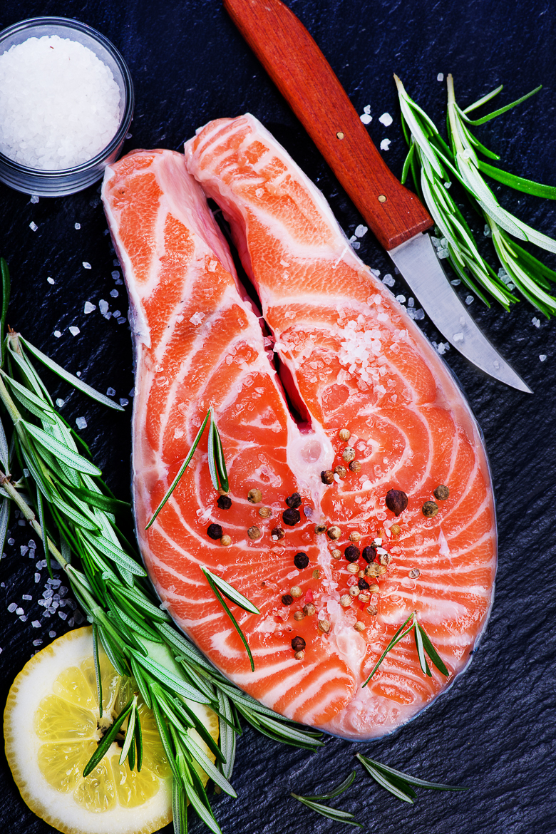 fresh salmon with rosemary on plate and on a table