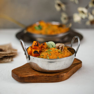 Two bowls of yellow daal topped with squash and limes wedges placed on trays