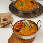 Two bowls of yellow daal topped with squash and limes wedges placed on trays with roti on the side