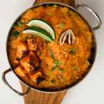 a bowl of yellow daal topped with butternut squasg and lime wedges placed on a wooden tray
