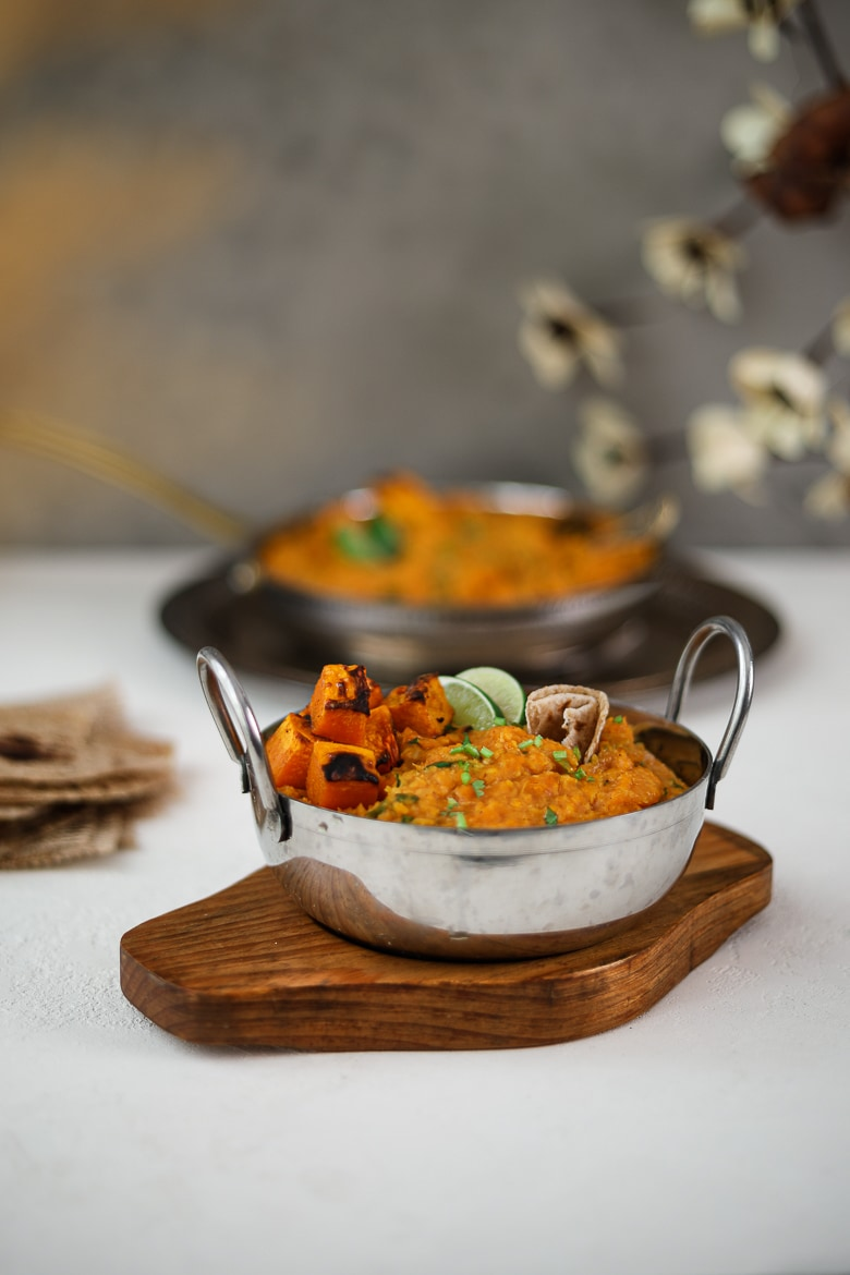 Two bowls of yellow daal topped with squash and limes wedges placed on trays - for Ramadan 2021