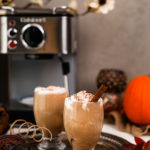 two glasses of iced pumpkin spice latte on a tray with an espresso machine in the background and other fall props