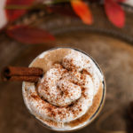 flatlay shot of the top of a glass with whipped cream sprinkled with cinnamon displayed on a tray,