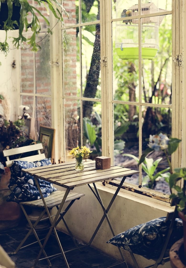 A relaxed cafe scene with wooden table and 2 chairs near a window overlooking a garden space