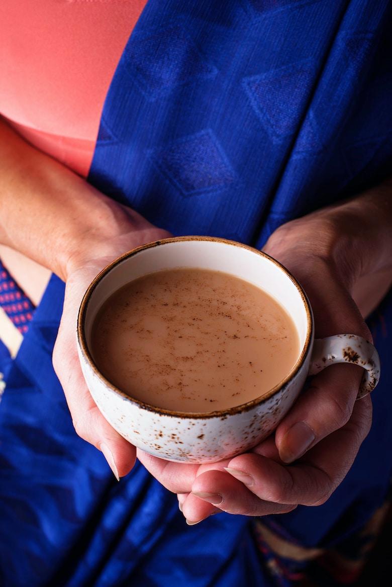 Woman in sari holding a cup of masala chai tea
