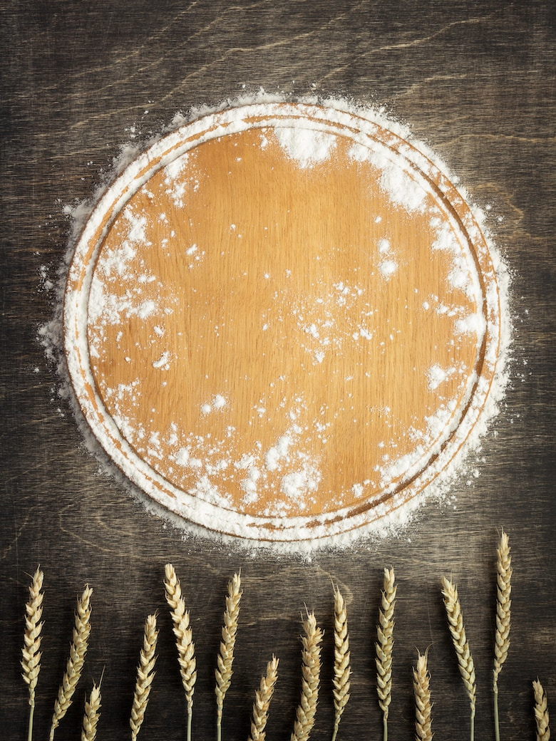 wheat flour and cutting board on wooden background, top view