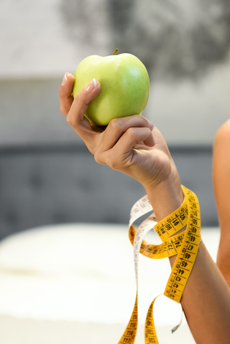 Woman holding a fresh healthy green apple in her hand with a tape measure wound round her arm in a diet and weight loss concept in close up