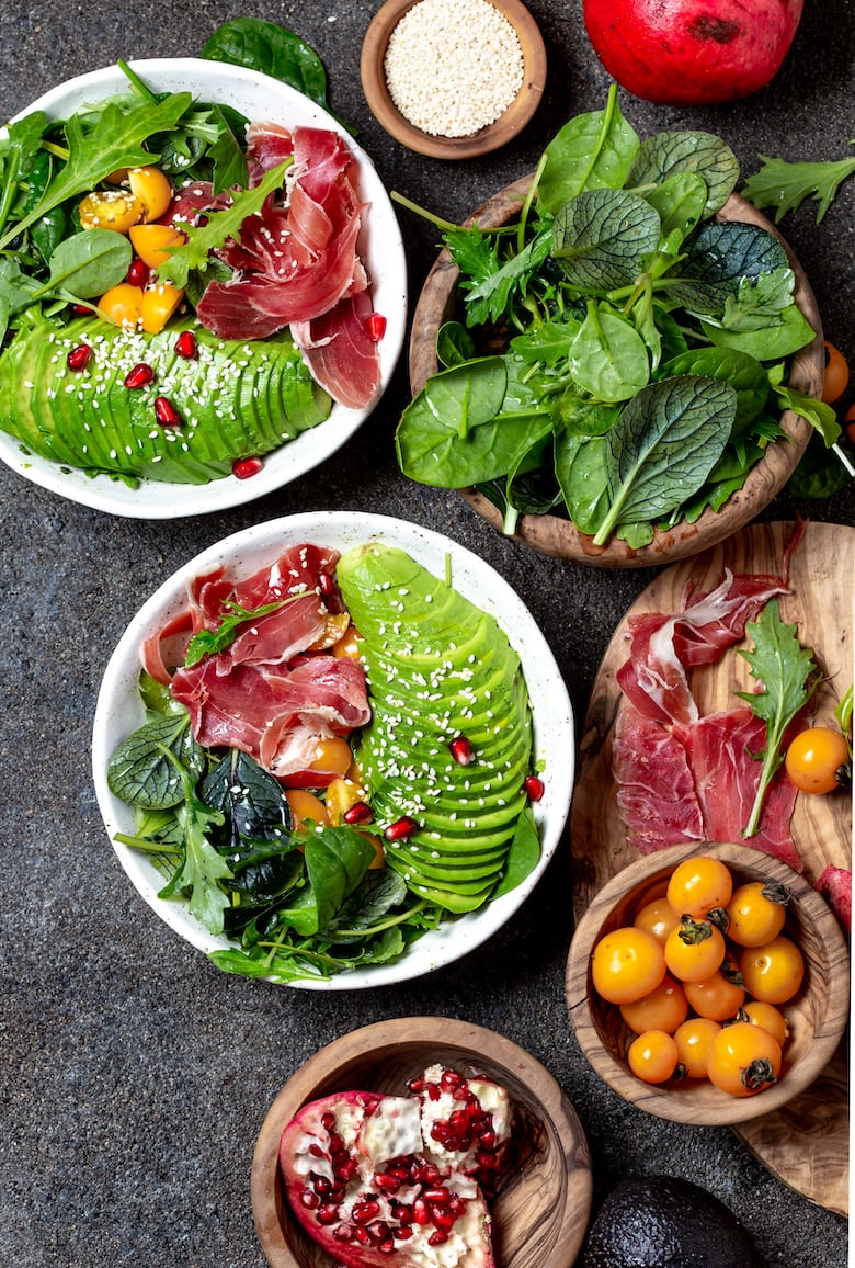 Low carbs bowl. Fresh salad with green spinach, rucola, avocado an ham serrano in white bowl, gray background, top view.