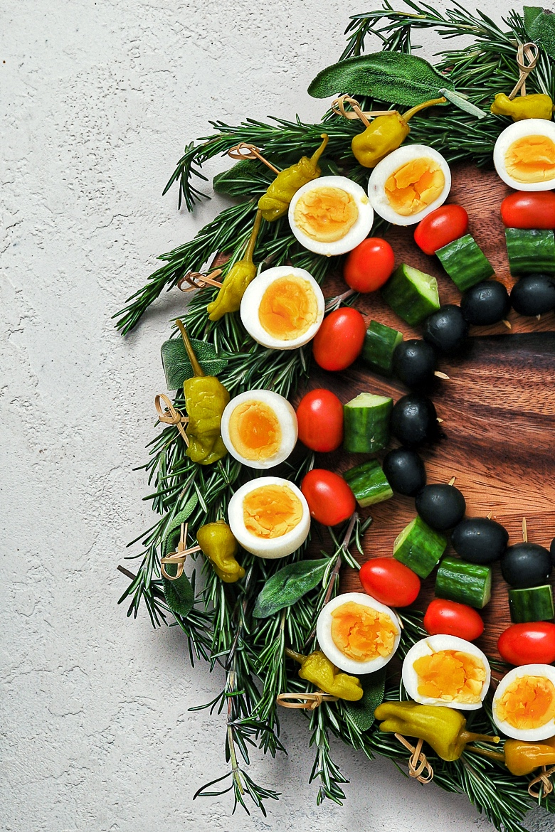 a low carb appetizer created as a edible holiday wreath, made with boiled eggs and vegetables on skewers on a bed of herbs - flatlay