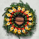 an edible holiday wreath made with boiled eggs and vegetables on skewers on a bed of herbs - flatlay