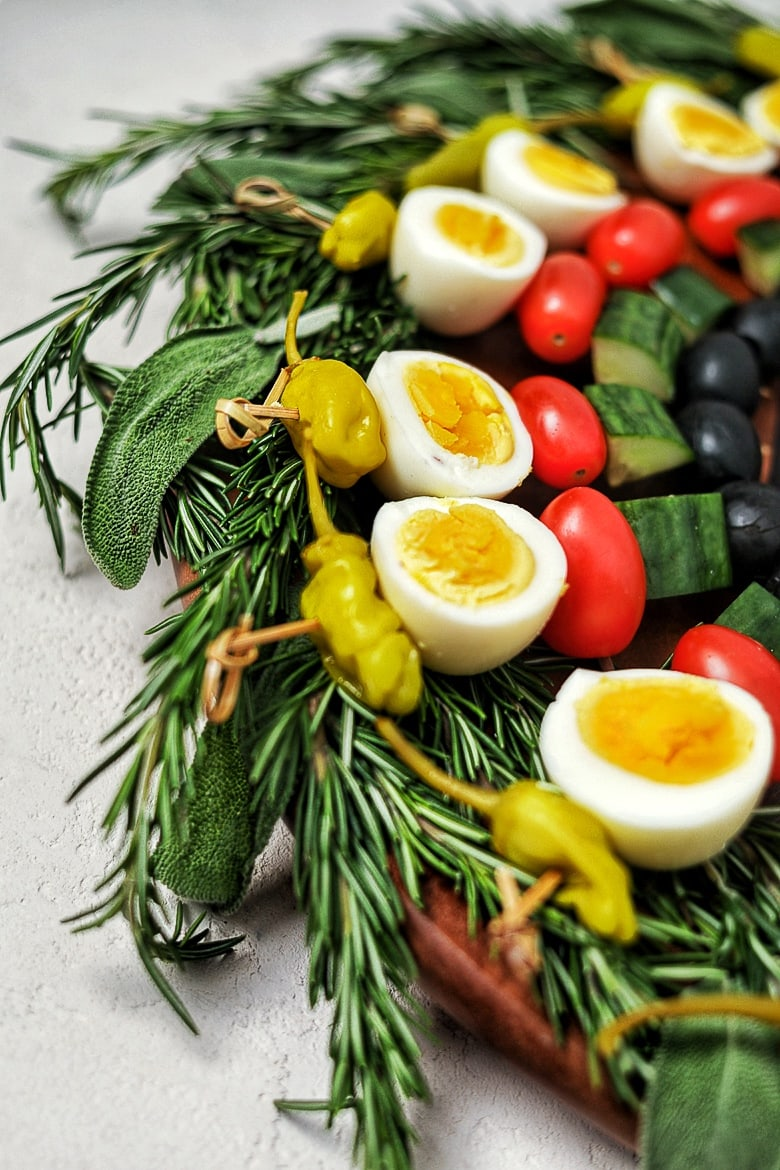 a low carb appetizer created as a edible holiday wreath, made with boiled eggs and vegetables on skewers on a bed of herbs