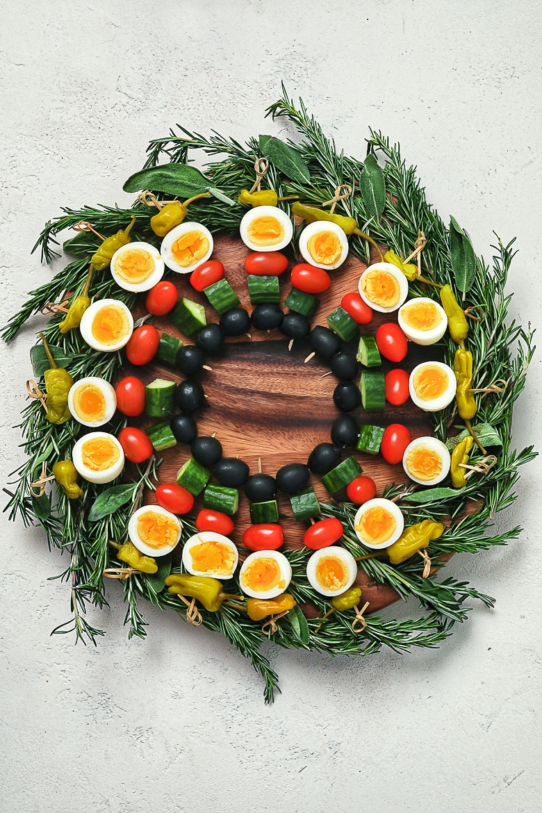 an edible holiday wreath made with boiled eggs and vegetables on skewers on a bed of herbs - flatlay.