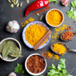 Set of Indian food cooking ingredients. Traditional Indian assorted spices and herbs. Curry, turmeric, cardamom, garlic, pepper, cilantro, cinnamon. Preparing exotic meal. Top view, close up