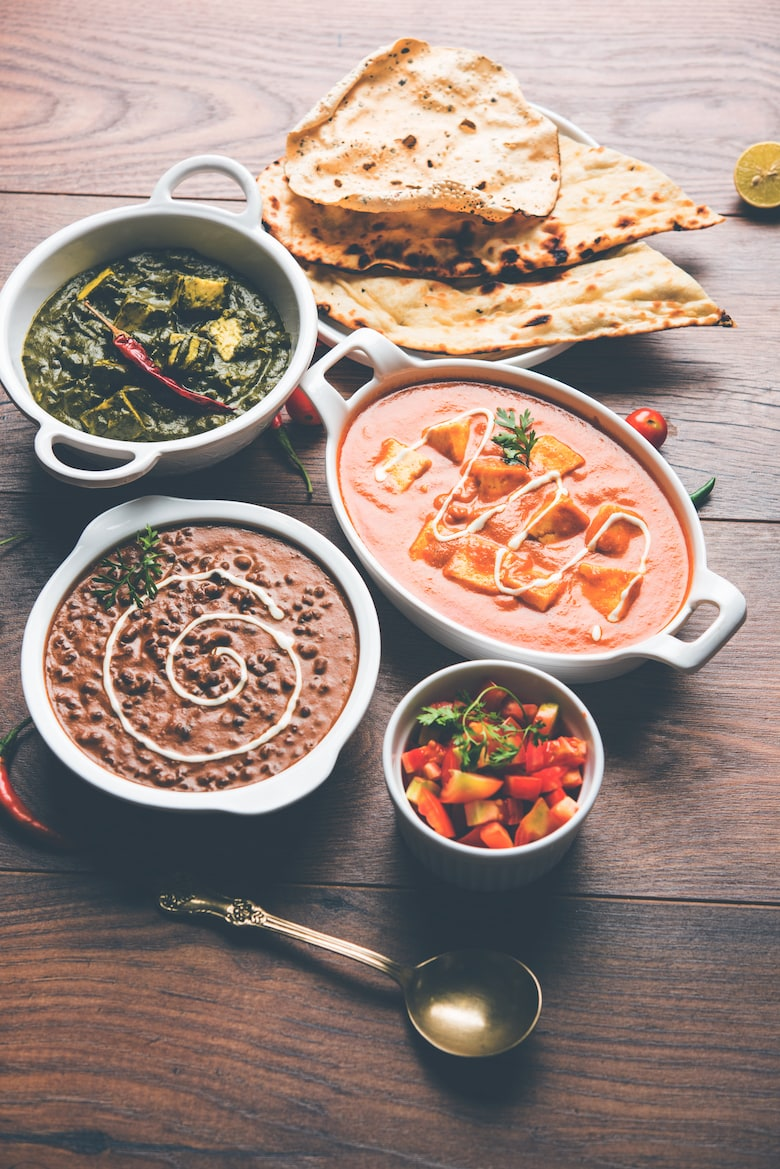 bowls of desi food dishes (indian cuisine) on a wooden table with naan bread