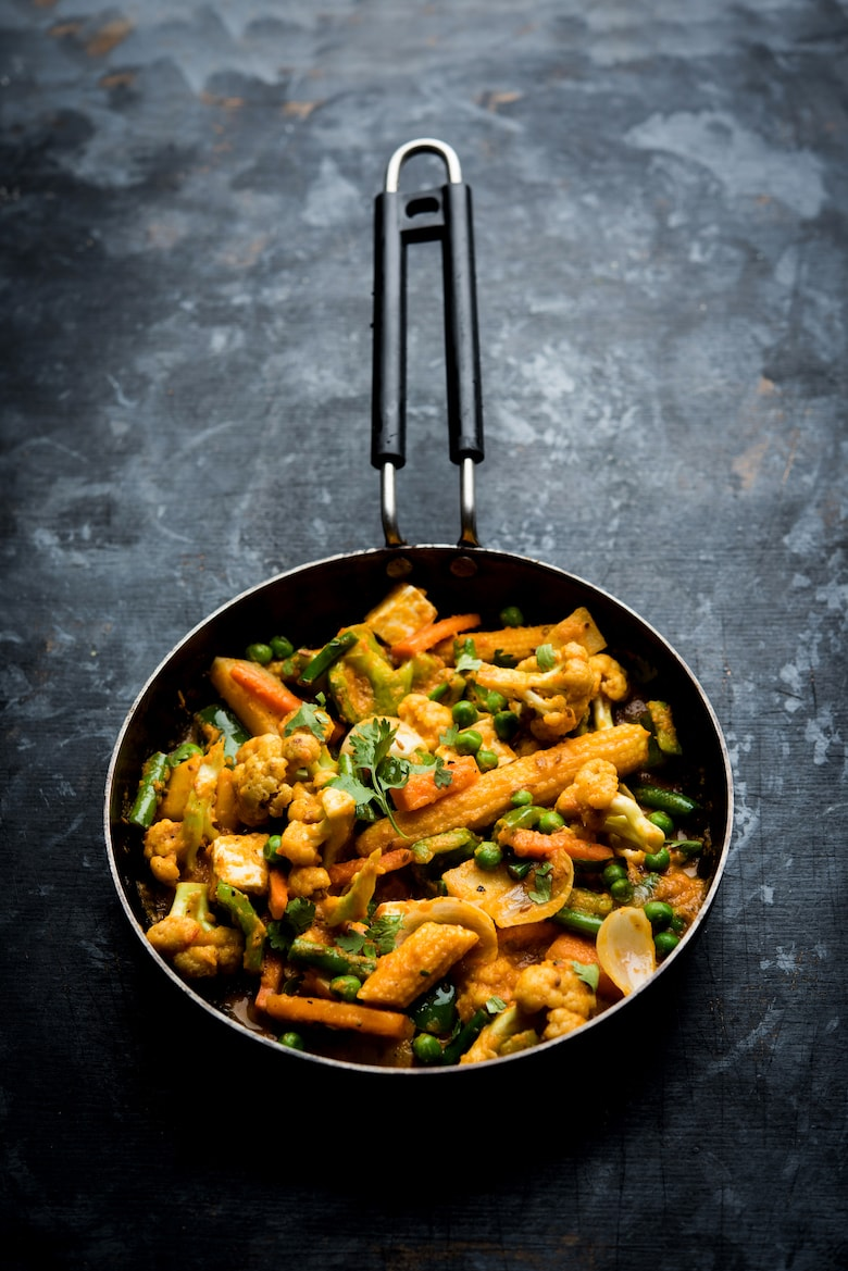 pan of Indian vegetable curry on a grey backdrop
